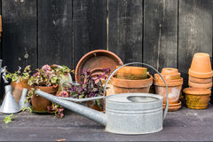 Romantyczny idylliczny roślina stół w ogródzie z starymi retro kwiatu garnka garnkami, ogrodowymi narzędziami i roślinami, obraz royalty free