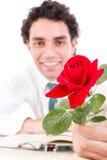 Romantyczny mężczyzna mienie wzrastał z książką i szkłami na stole Zdjęcia Royalty Free