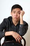 Romantyczny młody Azjatycki mężczyzna obsiadanie na krześle zdjęcia royalty free