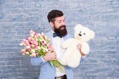 Romantyczny m??czyzna z kwiatami i misiem Romantyczny prezent Macho dostaje gotowa romantyczna data Mężczyzna odzieży smokingu łę zdjęcie royalty free