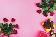 Romantyczny mieszkanie kłaść z czerwonymi różami i prezentów pudełkami na różowym tle Obraz Stock