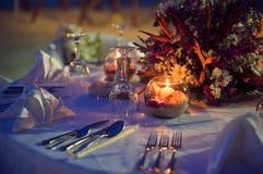 Romantyczny obiadowy położenie na plaży przy zmierzchem Zdjęcia Royalty Free