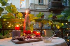 Romantyczny obiadowy stół na balkonie z świeczkami, czekoladami i owoc, Obrazy Stock