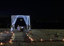 Romantyczny obiadowy ustawianie na plaży przy nocą Obrazy Royalty Free