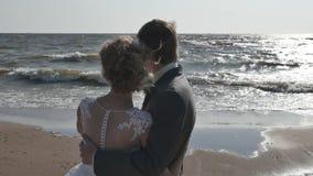 Romantyczny pary obejmowanie przy zmierzchem cieszył się oglądający zmierzch nad oceanem Mężczyzna i kobiety pozycja w pełnym cie zdjęcie wideo