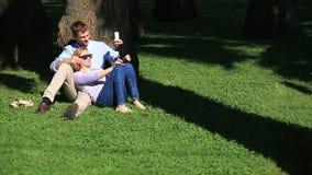 Romantyczny pary obsiadanie pod drzewkiem palmowym Dziewczyna na podołku facet Kochająca para odpoczywa w parku na trawie zbiory