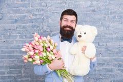 Romantyczny prezent Macho dostaje gotowa romantyczna data M??czyzna odzie?y smokingu ??ku krawata b??kitny chwyt kwitnie bukiet i obrazy royalty free