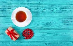 Romantyczny prezent z czerwonym łękiem i filiżanka herbata na drewnianym tle Prezent dla kobiety ` s dnia kubek herbaty odosobnio Fotografia Royalty Free