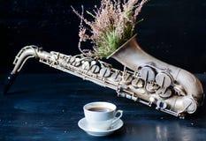 Romantyczny ranek z filiżanką i kwiatami w saksofonie zdjęcie royalty free
