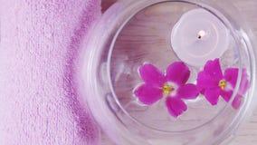 Romantyczny skład z fiołkiem i świeczką kwitnie unosić się w pucharze woda zdjęcia royalty free
