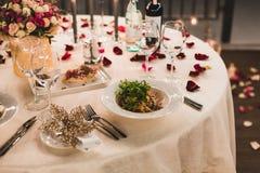 Romantyczny stołowy położenie z winem, pięknymi kwiatami w pudełku, pustymi szkłami, różanymi płatkami i świeczkami, obrazy stock
