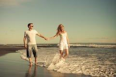 Romantyczny szczęśliwy mężczyzna i kobieta dobieramy się odprowadzenie na plaży Zdjęcie Royalty Free