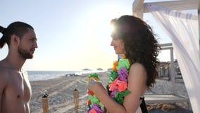 Romantyczny wakacje dla kochającej pary morzem stawiają na szyi facet i dziewczyna, Hawaje lei, Pogodna plażowa tropikalna wyspa  zdjęcie wideo