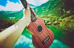 Romantyczny widok ukulele gitary chwyt w ręce, góry dalej Zdjęcie Royalty Free
