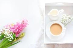 Romanze Frühstück, Tasse Kaffee, Milchkrug und Kuchen des Morgens mit Dekor der rosa Hyazinthe junge gelbe Blume gegen weißen Hin Lizenzfreie Stockfotografie