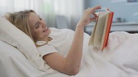 Romanzo contentissimo sorridente della lettura dell'adolescente circa amore romantico, trovantesi a letto stock footage