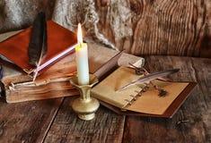 Romanzo del libro e della piuma vicino ad una candela Immagini Stock Libere da Diritti