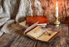 Romanzo del libro e della piuma vicino ad una candela Fotografie Stock