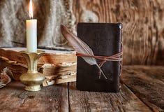 Romanzo del libro e della piuma vicino ad una candela Fotografie Stock Libere da Diritti
