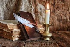Romanzo del libro e della piuma vicino ad una candela Immagine Stock Libera da Diritti
