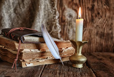 Romanzo del libro e della piuma vicino ad una candela Immagine Stock