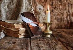 Romanzo del libro e della piuma vicino ad una candela Fotografia Stock