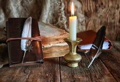 Romanzo del libro e della piuma vicino ad una candela Fotografia Stock Libera da Diritti