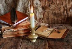 Romanzo del libro e della piuma vicino ad una candela Immagini Stock
