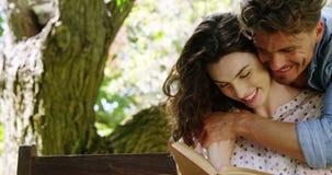 Romanzo romantico della lettura delle coppie in parco archivi video