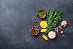 Romarin frais et épices mélangées sur la vue supérieure en pierre noire de table Ingrédients pour la cuisson Fond de nourriture photographie stock libre de droits