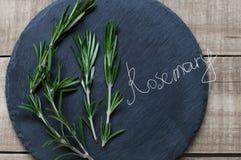 Romarin frais sur le panneau noir d'ardoise sur la table en bois et l'ha drôle Photo stock