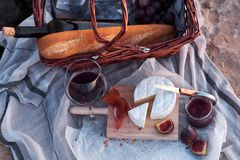 Romatic picnic on the beach. Beautiful romantic picnic composition with basket, red wine, bread, jam, cheese and jamon stock photos