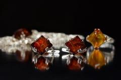 Rombo de prata dos brincos do close up com âmbar Báltico natural autêntico na superfície do preto Imagem de Stock Royalty Free