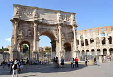 Rome: Arch of Constantine and Colosseum. ROME, ITALY - 2 JULY 2016: Tourists flock around the Arch of Constantine and the Colosseum Royalty Free Stock Images