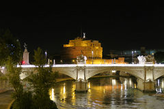 Rome a bridge on Tiber river before Castel SantAngelo at night. Ponte SantAngelo castle visible in the background at Rome Italy stock image