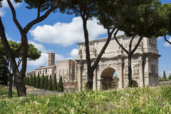 Rome central archeological area. Arch of Constantine and Temple of Venus ancient ruins with green grass, in the historic center of Rome Royalty Free Stock Photo