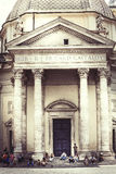 Rome, church monuments and tourists. Some tourists sitting on the steps at the foot of the church in Piazza del Popolo. Santa Maria di Montesanto church. Twin stock image