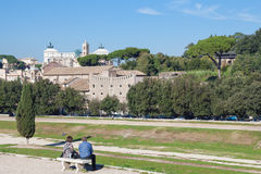 Rome city view. Rome, Italy - November 7, 2015: Couple siting on the bench and enjoying the view of the city at sunny autumn day Stock Photo