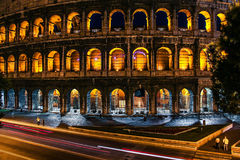 Rome Colosseum by night with yellow lighted archs and long exposured car lights.  Stock Photos