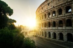 Rome Colosseum at sunrise in Rome, Italy. Rome Colosseum at morning sunrise and crowded street of Rome , Italy . The Colosseum was built in the time of Ancient royalty free stock photos