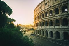 Rome Colosseum at sunrise in Rome, Italy. Rome Colosseum at morning sunrise and crowded street of Rome , Italy . The Colosseum was built in the time of Ancient stock image
