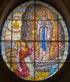 Rome - fönsterrutan av jungfruliga Mary av Lourdens i kyrkliga Chiesa di Santa Maria Annunziata arkivbild