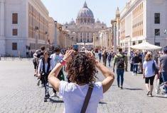ROME, ITALIË - APRIL 27, 2019: De jonge vrouw fotografeert de Basiliek van Heilige Peter, Rome, Italië royalty-vrije stock afbeelding