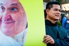 Rome, Italië - 20 januari 2019: een jonge Aziatische priester draagt een grote banner met een binnen beeld van paus Francis in ca stock afbeelding