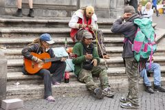 Rome, Italië, 10 Oktober, 2011: De daklozen spelen de gitaar op de stappen van een Katholieke tempel stock fotografie