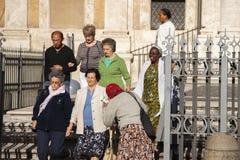 Rome, Italië, 9 Oktober, 2011: Oudere vrouw die om aalmoes bij de ingang aan een Katholieke kerk vragen stock foto's