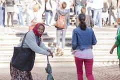 Rome, Italië, 9 Oktober, 2011: Oudere vrouw die om aalmoes bij de ingang aan een Katholieke kerk vragen stock foto