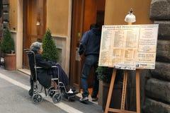 Rome Italien - April 9, 2017: Get för anhörigvårdare och för rörelsehindrad kvinna Royaltyfria Bilder
