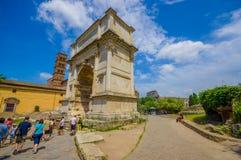 ROME ITALIEN - JUNI 13, 2015: Folket skriver in till Roman Forum, stor stenbåge med roman bokstäver Träd lite varstans stället Arkivbild