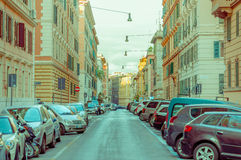 ROME ITALIEN - JUNI 13, 2015: Lång typisk gata i Rome med bilar på sidor, trevlig sikt med gatabelysning Royaltyfria Bilder